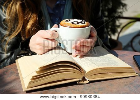 Hands holding cup of cappuccino in cafe, outdoors