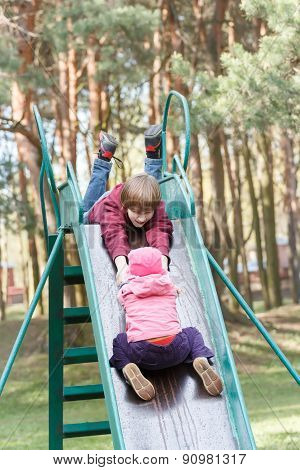 Sibling children are playing on playground slide made of metal together in pine park