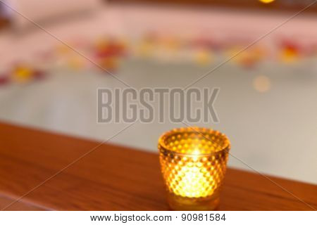 Candle In A Glass Candle Holder Near Jacuzzi. Abstract Blur Background With Bokeh