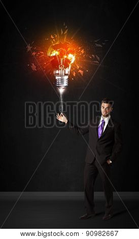 Businessman with an explosion bulb on black background