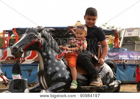 Black African Boys Riding On Electronic Horse