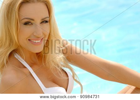 Close Up Portrait of Blond Woman Wearing White Bikini Smiling at Camera Next to Swimming Pool