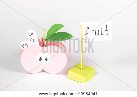 paper half pink apple with vitamin and card with word