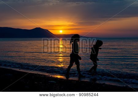 Two girls walking along the beach during sunset