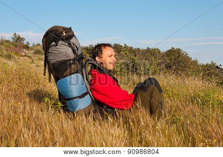 Hikers with backpack sitting on grass in mountain and looking into the distance