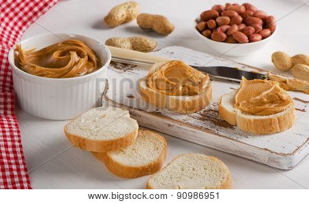 Toast With Peanut Butter  And Peanuts On A Wooden Board