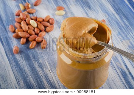 Peanut Butter In  Jar On A Blue Background.