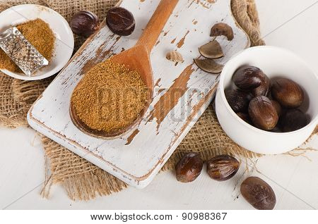 Raw Organic Ground  Nutmeg On  White Wooden Cutting Board.