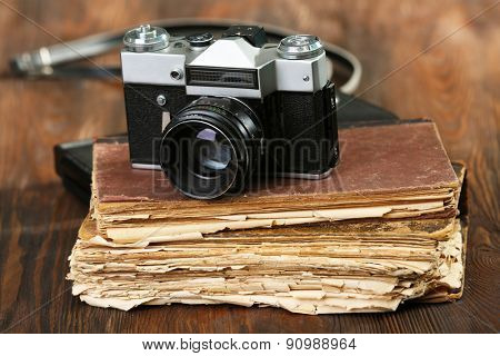 Retro camera with old book on table on green background