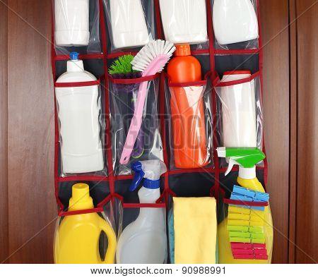Different detergents in hanging bag wooden door
