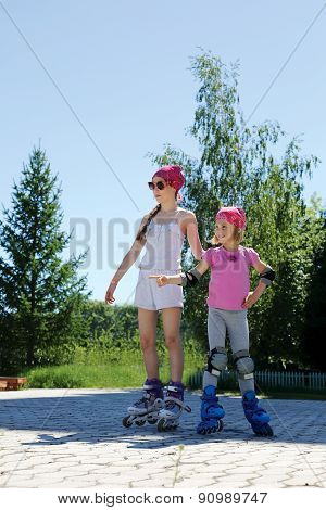 Two Girls Skate On Roller Skates In The Park In The Summer.