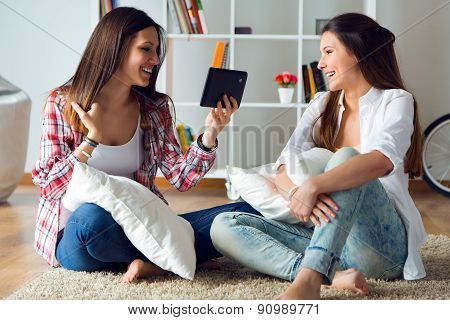 Two Beautiful Young Woman Friends Using Digital Tablet At Home.