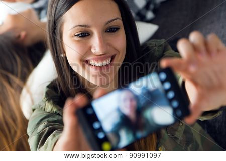 Two Beautiful Young Woman Using Mobile Phone At Home.
