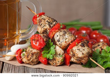 Traditional chicken or turkey kebab skewer barbecue meat with vegetables, green onion and beer on ba