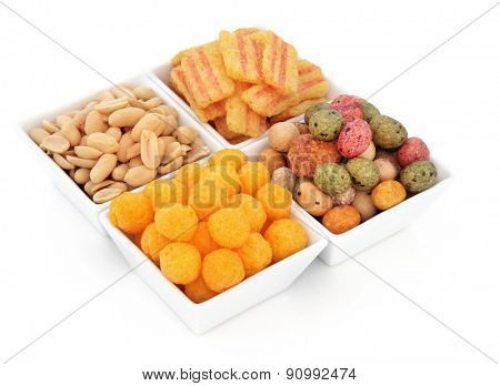Savoury snack party food selection in square porcelain bowls over white background.