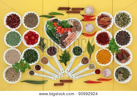 Herb and spice selection in measuring spoons, a heart shaped dish, crinkle bowls and loose over wooden yellow background.