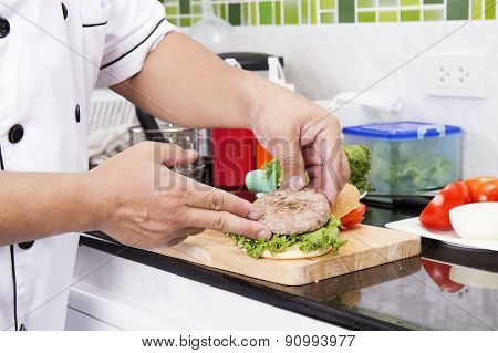 Chef Putting Beef Hamburger On The Bun