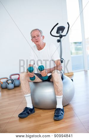 Old man sitting on exercise ball in fitness studio