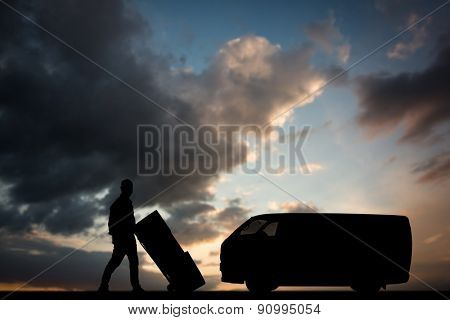Happy delivery man pushing trolley of boxes against blue and orange sky with clouds