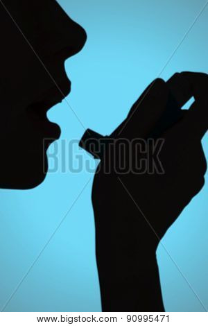 Close up of a woman using an asthma inhaler against blue background with vignette