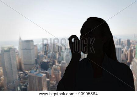 Pretty blonde using an asthma inhaler against new york skyline