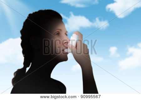 Woman using inhaler for asthma against blue sky