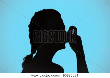 Woman using inhaler for asthma against blue background with vignette