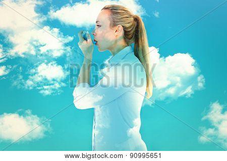 Beautiful blonde using an asthma inhaler against blue sky