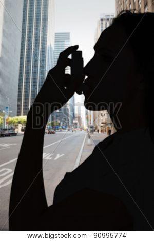 Asthmatic brunette using her inhaler against new york street