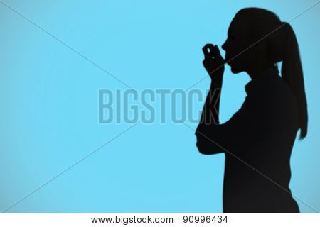 Beautiful blonde using an asthma inhaler against blue background with vignette