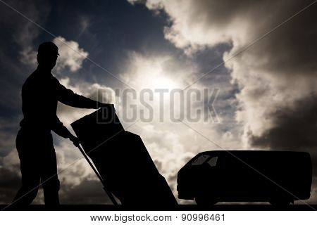 Happy delivery man pushing trolley of cardboard boxes against dark sky with white clouds