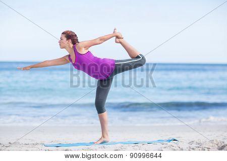 Brunette doing yoga on exercise mat at the beach