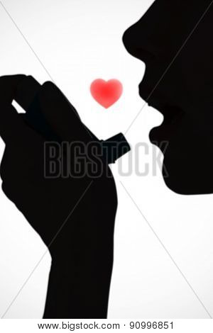Close up of a woman using an asthma inhaler against white background with vignette