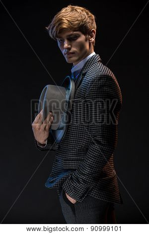 Redheaded man at a plaid suit with hat in hand