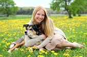 stock photo of shepherd dog  - A happy woman is sitting outside in a flower meadow in the country hugging her German Shepherd Mix breed dog - JPG