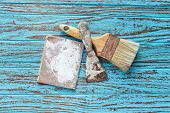 stock photo of trowel  - paintbrush trowel sandpaper still life wood teak table antique blue old style - JPG