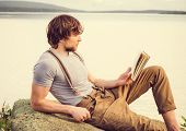 foto of swag  - Young Man reading book outdoor with scandinavian lake and mountains on background Education and Lifestyle Travel concept - JPG