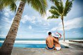 pic of couple sitting beach  - Beach vacation couple on summer holidays - JPG