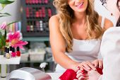 image of beauty parlor  - Woman receiving manicure in beauty parlor - JPG