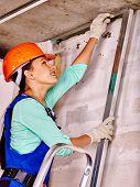 stock photo of millwright  - Happy woman in builder uniform and orange helmet at work - JPG
