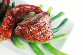 stock photo of veal  - served grilled beef veal fillet entrecote on a white plate with peppers and green peas on long plate isolated on white background - JPG