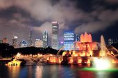 image of fountains  - Chicago skyline with skyscrapers and Buckingham fountain in Grant Park at night lit by colorful lights - JPG