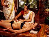 stock photo of panchakarma  - Young woman having stomach massage oil Ayurveda spa treatment - JPG