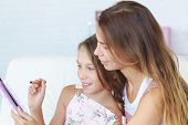 image of preteens  - Mother helps her preteen daugher learning ipad together - JPG