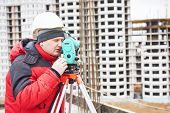 pic of theodolite  - surveyor working with theodolite transit equipment at construction site  - JPG