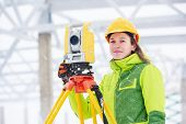 stock photo of theodolite  - female surveyor worker working with theodolite transit equipment at building construction site outdoors - JPG