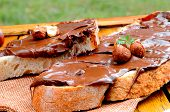 pic of hazelnut  - Two slices of bread with chocolate cream and hazelnuts on a wooden table outdoors - JPG