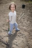 picture of hoe  - Girl standing with hoe during preparation to plant - JPG