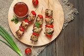 image of kebab  - Tasty fried turkey or chicken kebab skewers bbq meat on wooden round desk with tomatoes - JPG