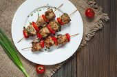 stock photo of kebab  - Traditional delicious turkey kebab skewer barbecue meat with tomatoes and green onion on white dish - JPG